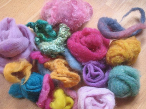 "First you need a selection of wool ""roving"".  It is basically fluffy un-spun dyed wool fiber.  This is the color palette we used."